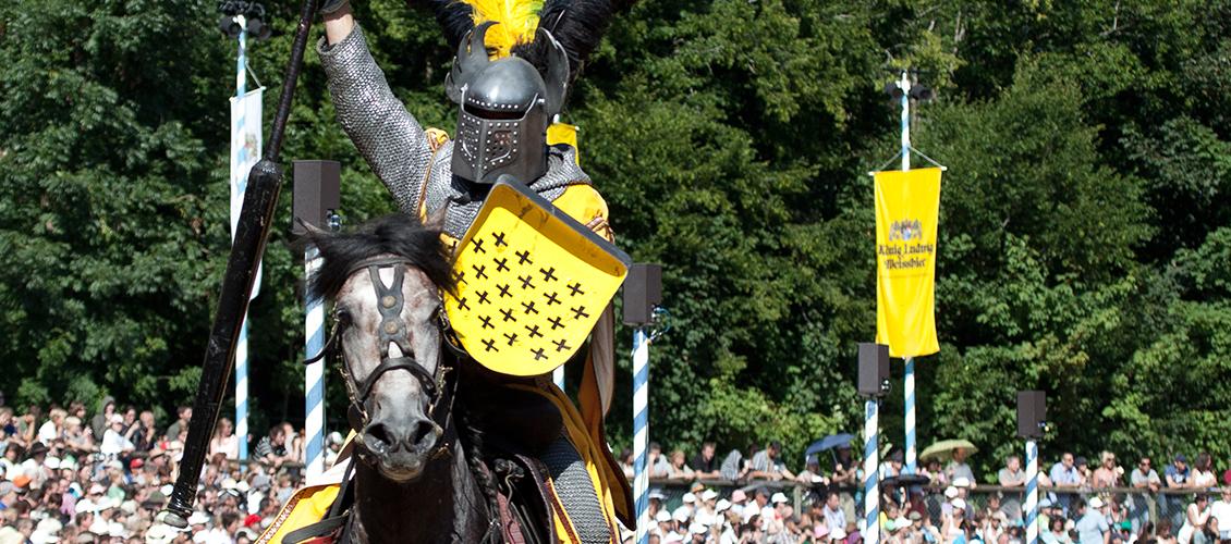Ein Ritter auf dem Pferd vor Zuschauern